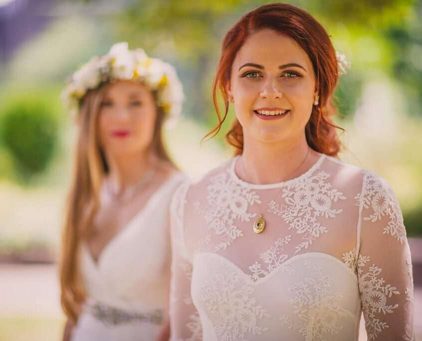 two brides smiling at each other on their wedding day