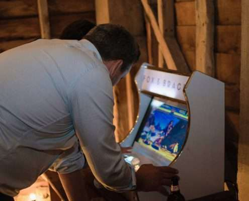 people playing an arcade machine at a wedding