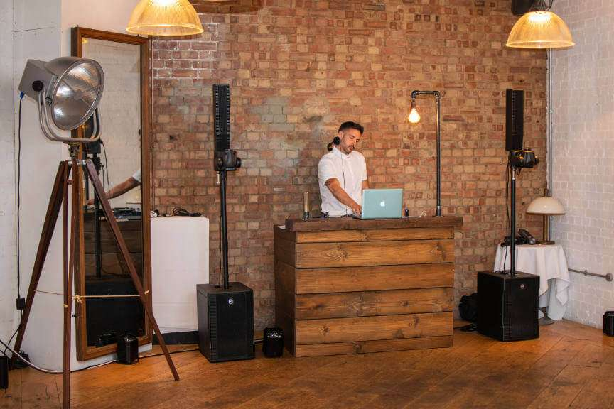 A dj behind a rustic dark oak DJ booth